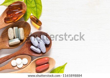 Variety of vitamin pills in wooden spoon on white background with green leaf, supplemental and healthcare product, flat lay surface #1165898884