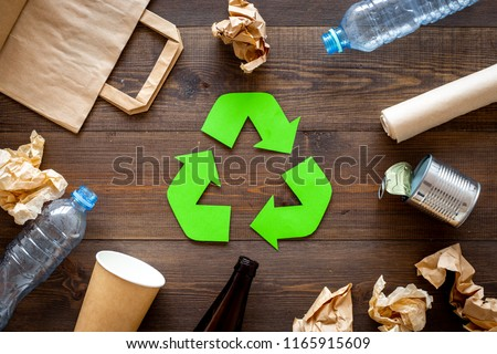 Recycling. Green recycle eco symbol. Recycled arrows sign near matherials for recycle and reuse on dark wooden background top view #1165915609