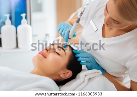 Cosmetology clinic. Professional female cosmetologist doing hydrafacial procedure while being a work Royalty-Free Stock Photo #1166005933