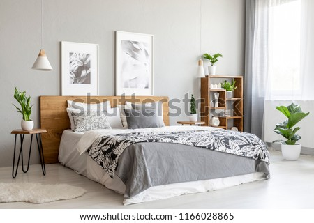 Patterned blanket on wooden bed in grey bedroom interior with plants and posters. Real photo #1166028865