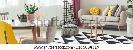 Panorama of chairs at dining table in living room interior with pouf on carpet next to settee. Real photo #1166034319
