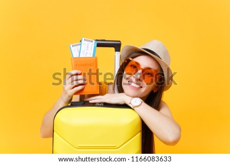 Fun tourist woman in summer casual clothes, hat, orange sunglasses with suitcase, passport isolated on yellow background. Passenger traveling abroad to travel on weekends getaway. Air flight concept #1166083633