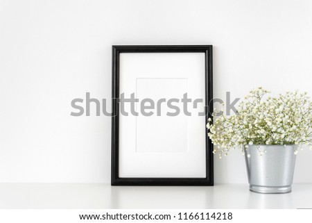 Black a4 frame mockup in interior. Frame mock-Up poster or photo frame and supplies and vase with flowers on table near white wall. Desk space, copy space. Background #1166114218