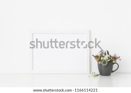 White a4 landscape portrait frame mockup with small bouquet of dried flowers in vase on white wall background. Empty frame, poster mock up for presentation design. Template frame for text, lettering