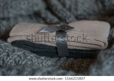 Closeup on a pack of beautiful pink grey socks with a bow made from wool and cashmere blend located on a knitted plaid. Comfy autumn winter background. Selective focus.  #1166215807