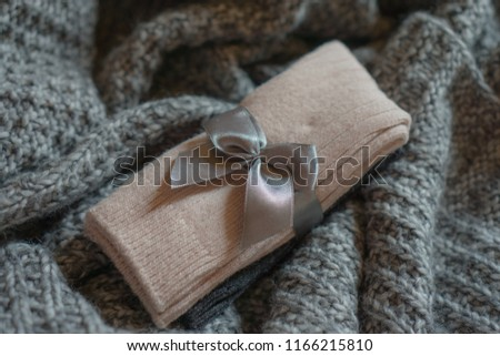 Closeup on a pack of beautiful pink grey socks made from wool and cashmere blend located on a knitted plaid. Cozy autumn winter background. Selective focus. Gift idea.  #1166215810