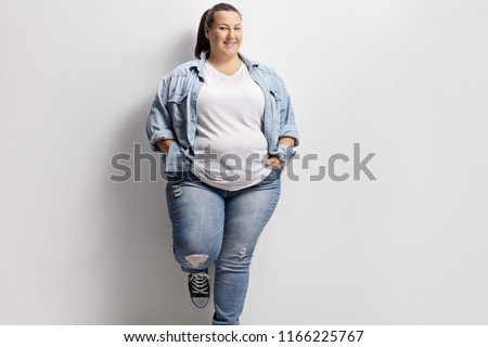 Young overweight woman in casual clothes standing against a wall #1166225767