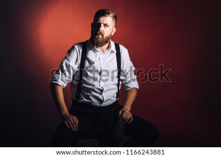 Portrait on a bearded man in white shirt and suspenders on black background in studio #1166243881