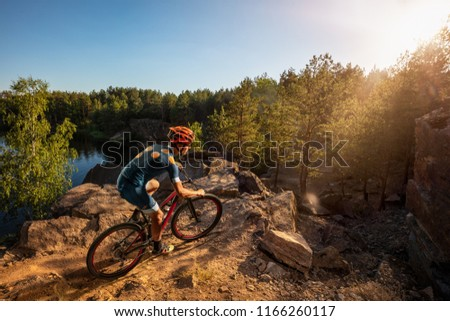 Cross-Country biker on stone trail near the lake. Male cyclist rides the rock #1166260117