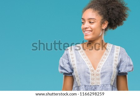 Young afro american woman over isolated background looking away to side with smile on face, natural expression. Laughing confident. #1166298259