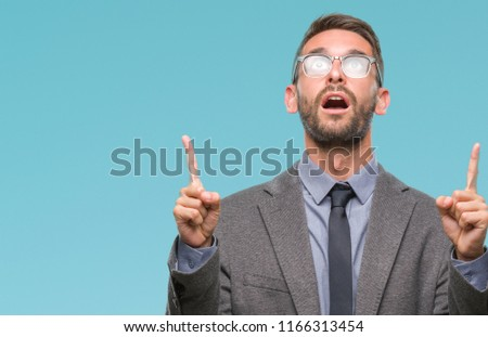 Young handsome business man over isolated background amazed and surprised looking up and pointing with fingers and raised arms. #1166313454