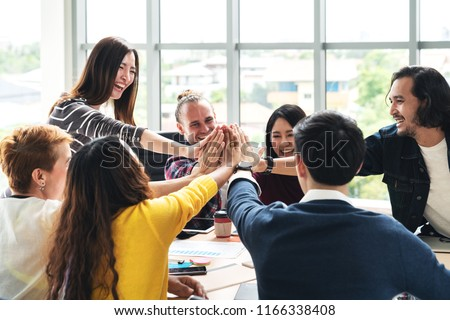 group of young multiethnic diverse people gesture hand high five, laughing and smiling together in brainstorm meeting at office. Casual business with startup teamwork community celebration concept. #1166338408