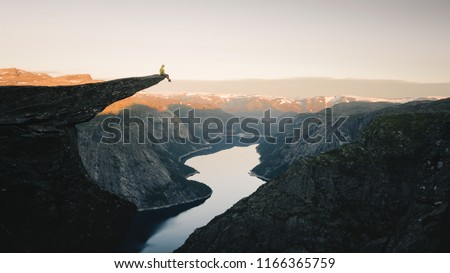 Man traveler on Trolltunga rocky cliff edge in Norway mountains Travel Lifestyle adventure emotional concept extreme vacations outdoor sunrise, tourist sitting alone Royalty-Free Stock Photo #1166365759