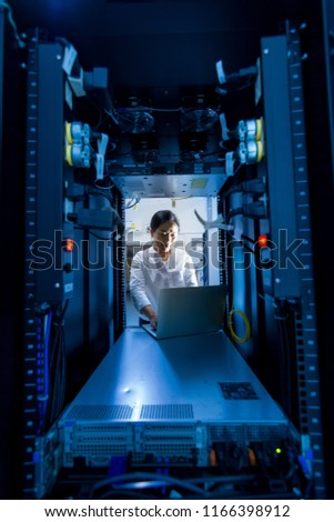 Asian female network administrator using laptop computer at networking rack cabinet on working in data center room #1166398912