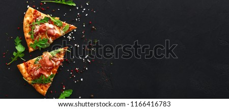 Slices of pizza with prosciutto and spices on black background, copy space, top view #1166416783