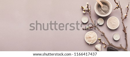 Preparing cosmetic black mask with spring flowers on gray background, copy space #1166417437