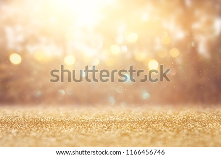 blurred abstract photo of light burst among trees and glitter golden bokeh lights #1166456746