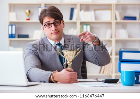 Businessman with golden cup in the office #1166476447