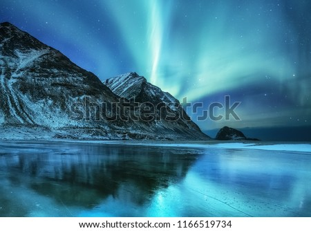 Aurora borealis on the Lofoten islands, Norway. Green northern lights above mountains. Night sky with polar lights. Night winter landscape with aurora and reflection on the water surface. #1166519734
