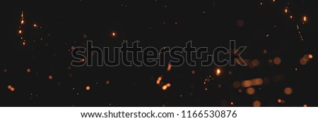 blurred sparks from fire in front of black backgound Royalty-Free Stock Photo #1166530876