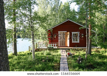 Finnish wooden lakeside cabin  exterior in wooded setting with path #1166556664