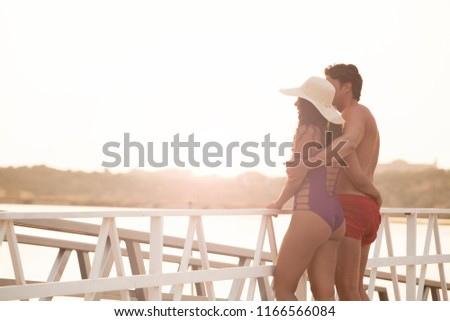 beautiful young couple embraced enjoying sunset on the hotel jetty #1166566084