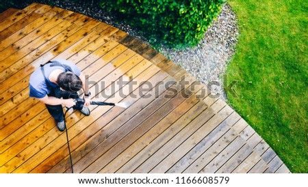 man cleaning terrace with a power washer - high water pressure cleaner on wooden terrace surface #1166608579