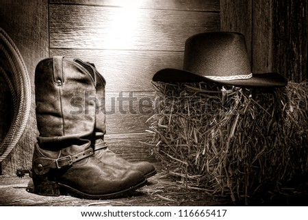 American West rodeo authentic leather roper boots and traditional western black felt hat on a bale of straw #116665417