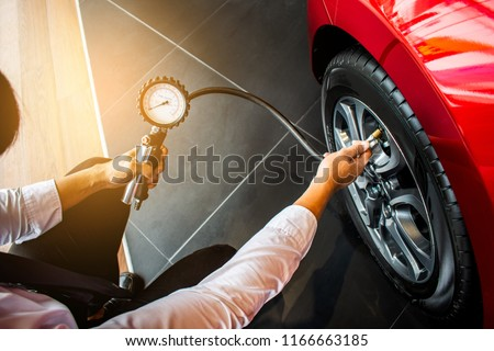 Asian man car inspection Measure quantity Inflated Rubber tirescar.Close up hand holding machine Inflated pressure gauge for car tyrepressure measurement for automotive, automobile image #1166663185