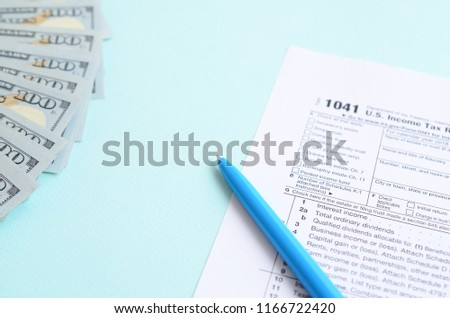 1041 tax form lies near hundred dollar bills and blue pen on a light blue background. US Income tax return for estates and trusts #1166722420