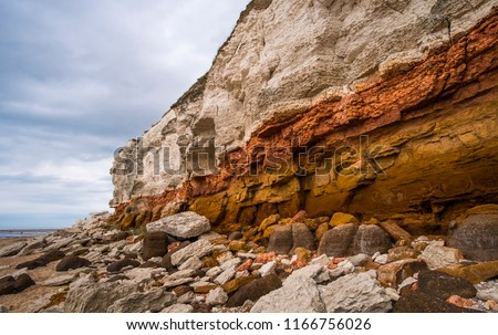 White chalk and red sandstone geological layer cliffs Royalty-Free Stock Photo #1166756026