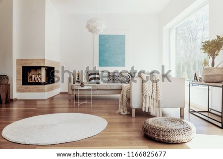 Large sky blue abstract art poster and a modern fireplace in a bright living room interior with dark hardwood floor #1166825677