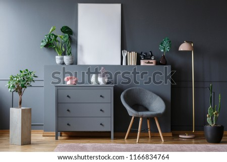 Real photo of an armchair between a cupboard and a lamp in dark living room interior with plants, ornaments and an empty poster #1166834764