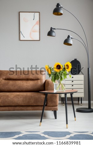 Sunflowers on wooden table next to brown sofa and black lamp in flat interior with poster. Real photo #1166839981