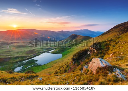Landscape photography. Stunning sunrise scenery in the alpine mountains. Mountain lake in the distance.