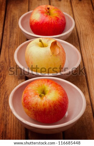 Apples in bowls on wooden table #116685448