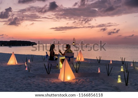 Couple is having a private event dinner on a tropical beach during sunset time: Honeymoon travel concept #1166856118