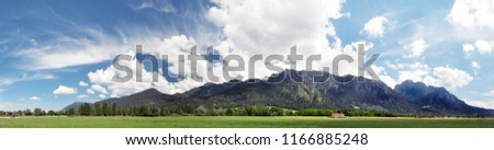 Panoramic view of Alps, Bavaria. Beautiful peaceful landscape, summertime. Blue sky with some white clouds, green meadows, mountains. Neuschwanstein castle on a right side of the picture far away
