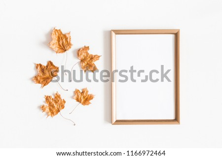 Autumn composition. Golden leaves, photo frame on white background. Autumn, fall concept. Flat lay, top view, copy space