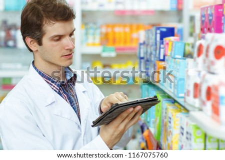 Side view of serious and concentrated worker of pharmaceutical industry wearing white coat and working. Male pharmacist holding laptop, pointing with hand on medicaments. #1167075760