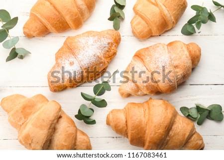 Tasty croissants on light wooden table #1167083461