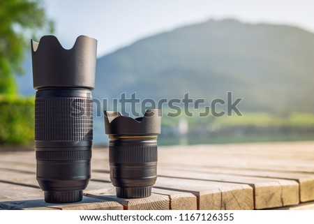Lenses of photo camera standing in a row. Zoom tele lens and wide angle lens with fixed focal length from dslr camera #1167126355