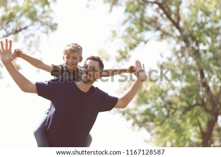 Little boy and his dad playing outdoors #1167128587