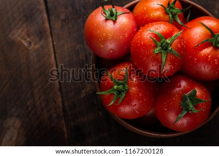 Fresh tomatoes in a plate on a dark background. Harvesting tomatoes. Top view #1167200128