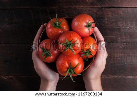 Fresh tomatoes in hands on a wooden background. Harvesting tomatoes. Top view #1167200134