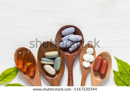 Variety of vitamin pills in wooden spoon on white background with green leaf, supplemental and healthcare product, flat lay surface #1167230344