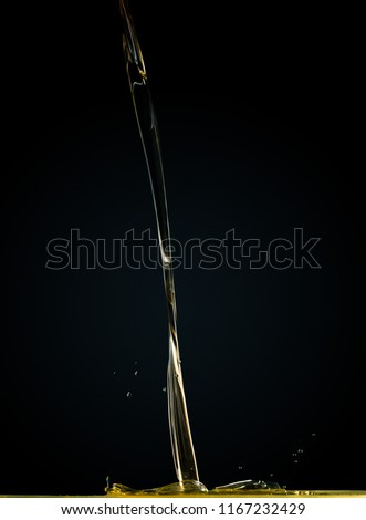 Close-up of oil and liquid pouring on dark background. Studio shutter freeze photography #1167232429