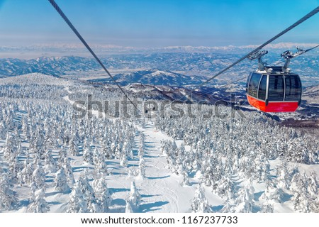 A scenic cable car flying over a piste in Zao hot spring & ski resort with a view of Juhyo (ice trees or snow monsters) all over the slope under blue clear sky on a sunny winter day in Yamagata, Japan #1167237733