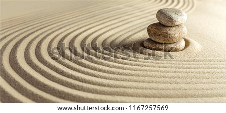 Japanese zen garden with stone in raked sand Royalty-Free Stock Photo #1167257569