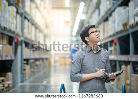 Asian manager man doing stocktaking of products in cardboard box on shelves in warehouse using digital tablet and pen. Male professional assistant checking stock in factory. Physical inventory count. #1167283660
